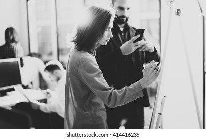 Creative managers meeting.Art director working with colleague designer startup project.Woman drawing new idea,analyze marketing plans.Blurred background,light effects,film effect.Wide,black and white