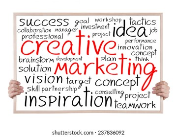 creative marketing and other related words handwritten on whiteboard with hands