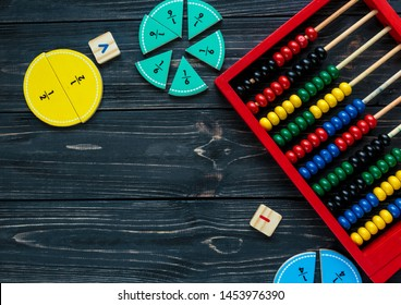 Creative Сolorful math fractions and abacus on dark background. Interesting funny math for kids. Education, back to school concept. Geometry and mathematics materials. Flat lay, top view