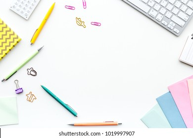 Creative mess on student's desk. Keyboard, notebook, stationery, on white background top view copy space
