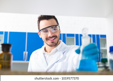 Creative method. Attractive bearded male laboratorian dressing in safety glasses while grinning and staring at bulb