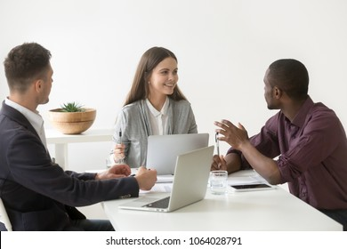 Creative millennial multiracial business team having discussion at office meeting, african manager sharing project ideas with smiling friendly female leader at group briefing, teamwork concept