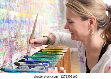 A Creative mindful woman painting with color palette