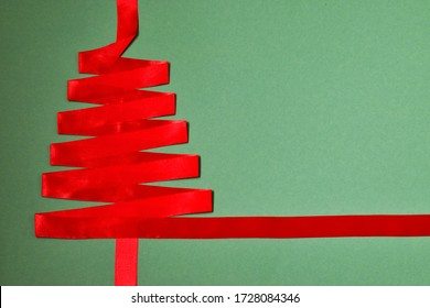 Creative mockup, flat composition with christmas tree made of red ribbon on green background with free space. Christmas concept.