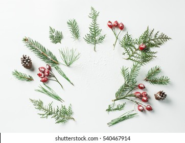 Creative mockup layout made of christmas tree and red holly berries branches with copy space snow on table. Homemade flat lay concept