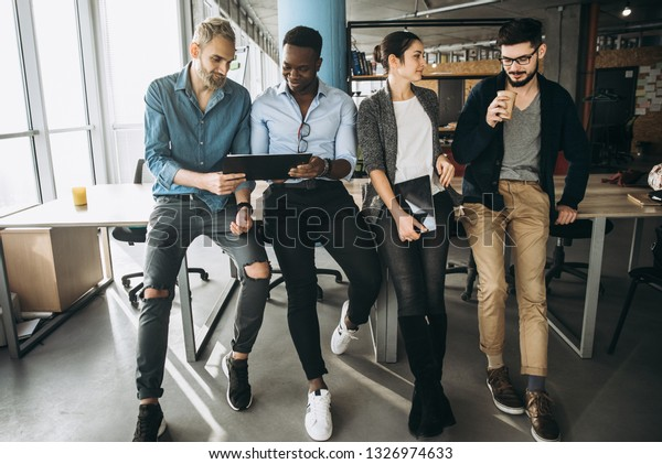 Creative modern office. Group of successful professionals stands near the table in their office and communicate to important themes