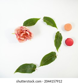 Creative music bass clef out of  a rose, fresh leaves and French macaron sweets on a white background  - Shutterstock ID 2044157912