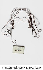 Creative music concept photo of retro vintage cassette with the tape forming human face hair and glasses on white background.