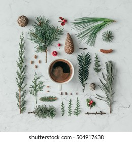Creative natural layout made of winter things with coffee cup on marble background. Flat lay.