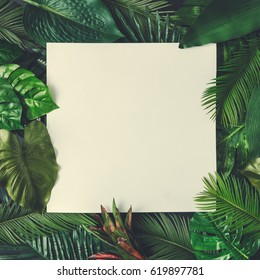 Creative nature layout made of tropical leaves and flowers With paper card note. Flat lay. Summer concept.