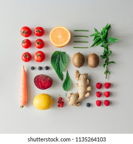 Creative neatly arranged food layout with fruits, vegetables and leaves on bright background. Minimal healthy food concept. Flat lay.