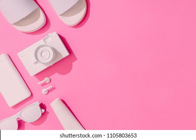 Creative neatly arranged layout with copy space and various summer objects on pastel pink background. Minimal vacation concept. Flat lay.