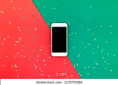 Creative New Year or Christmas smartphone mockup flat lay top view Xmas holiday celebration mobile phone on red green paper background. Template mock up 2019 2020