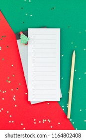 Creative New Year or Christmas todo list event planner mockup flat lay top view Xmas holiday celebration holiday schedule check list on red green paper background.