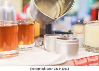 Creative occupation of candle making showing the pouring of liquid wax into jars - Shutterstock ID 1835460613