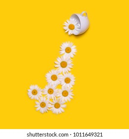 Creative original concept with a white cup and flowers on a yellow background. Large chamomiles pour out of the cup. Surrealistic composition with chamomile tea. Flat lay top view.