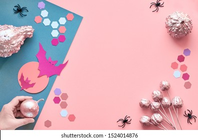 Creative paper craft Halloween flat lay on pink and grez split paper background with copyspace. Hand holding pink painted pumpkin,  bats with Moon, spiders and hexagons.
