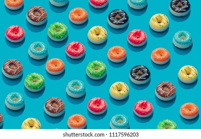 Creative pattern of colorful donuts on pastel blue background. Minimal food concept. Isometric.