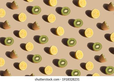 Creative pattern made with fresh lemons and kiwis against pastel beige background. Minimal summer fruit layout.