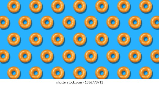Creative pattern yellow donuts flat lay on pastel blue background. Minimal sweet food concept. Surreal original doughnuts cake top view for bakery. Abstract summer donut dessert.