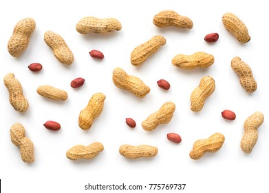Creative peanut pattern. Isolated unpeeled groundnut and kernels. Top view.