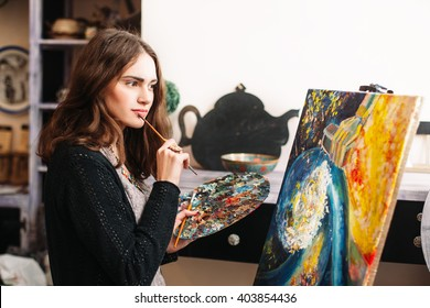 Creative pensive  painter paints a colorful picture. Closeup of painting process in art workshop Creative positive woman painter paints in her studio abstract picture.