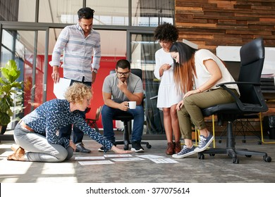 Creative people looking at project plan laid out on floor. Mixed race business associates discussing new project plan in modern office.