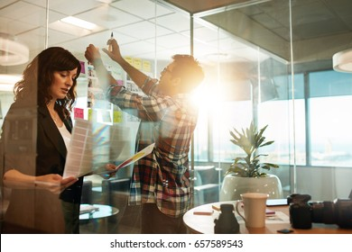 Creative people working on new project. Woman looking at photographs and man sticking at contact sheet on glass wall in office.