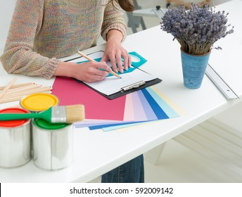 Creative people workplace. Close-up view of hands of young designer woman working with colour palette at office desk. Attractive model choosing colour samples for design project. Interior shot