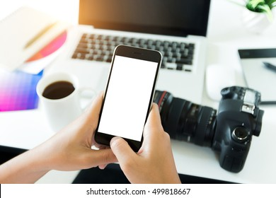 creative photographer holding phone white screen on workspace table, phone blank screen for adjustment mobile app