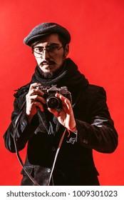 creative photographer posing in studio with camera in hands