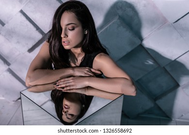 Creative photography. Reflection studio photography of passion alluring supermodel with long flowing shiny hair and olive-tinted skin leaning on mirror
