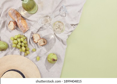 Creative picnic with wine and food flat lay. Minimal summer food background. Sunshine with shadow top view. Green pastel background