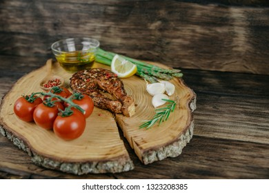 Creative plate in the form of a slice of wood with a baked salmon steak, cherry tomatoes, garlic, seasonings, rosemary, asparagus,lemon and olive oil. Wooden background.