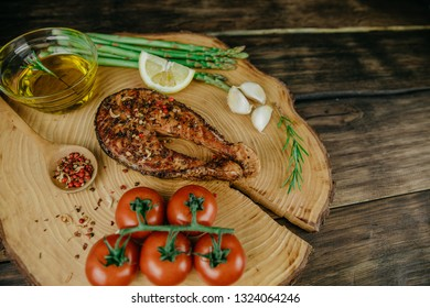 Creative plate in the form of a slice of wood with a baked salmon steak, cherry tomatoes, garlic, seasonings, rosemary, asparagus,lemon and olive oil. Wooden background. Closeup