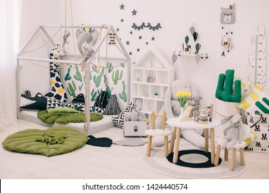 Creative playroom interior decorated with colorful lamps, cactus pillow