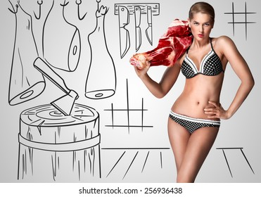 Creative portrait of a beautiful sexy female butcher in bikini holding raw meat on her shoulder on sketchy background of a butcher shop.