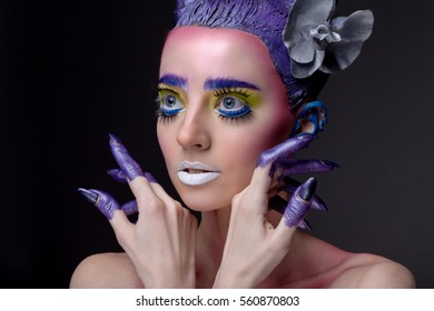 Creative portrait of a beautiful woman with art make up on gray background. With his hands in the face. painted blue fingers.