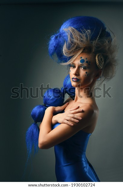 Creative portrait of female model with creative make-up and blue hairstyle