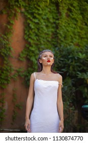 creative portrait of woman in white vintage dress with fashion makeup in old city