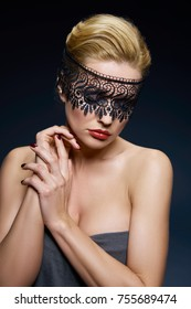 Creative portrait of a young woman in a lace mask. Blonde. Studio portrait.