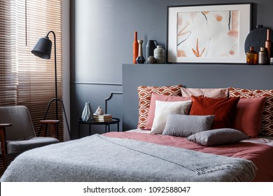 Creative poster on black bedhead above cozy bed with decorative cushions and gray blanket in bedroom interior with metal lamp and vintage armchair. Real photo
