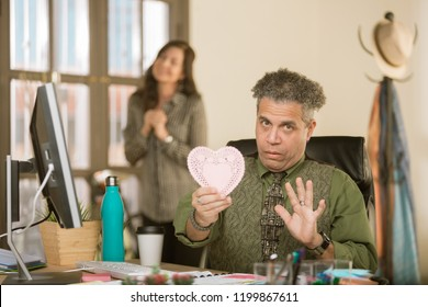Creative professional man reacting negatively  to Valentine message from coworker