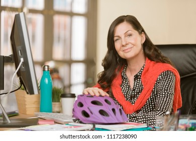 Creative professional woman at her desk with a bicycle helmet