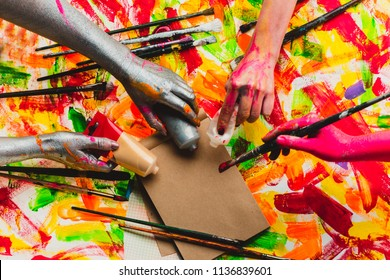 Creative project. Beautiful background. Art. The collective. Teambuilding. Four colored hands. Multi-color photo. Central composition. Filling the space. Work and fun.