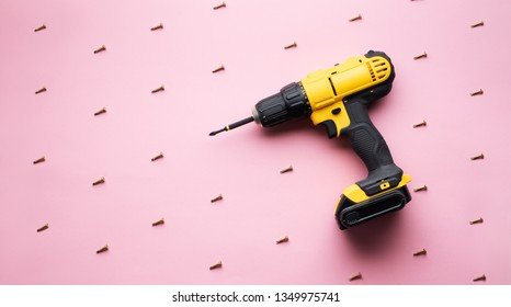 Creative provocation: a yellow screwdriver on a pink background and small screws.
