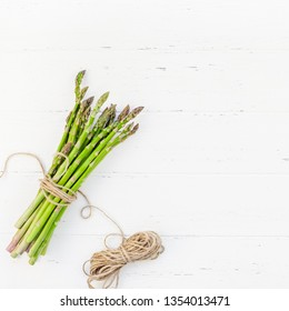 Creative scandinavian style flat lay top view mockup of fresh green asparagus on white wooden table background copy space. Minimal house cooking concept mock up for blog or recipe book