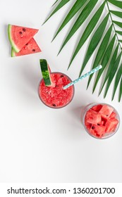 Creative scandinavian style flat lay top view of fresh watermelon slices smoothie drink in glass on white table background copy space. Minimal summer fruits concept for blog or recipe book