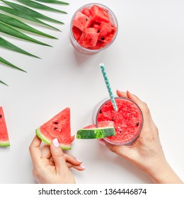 Creative scandinavian style flat lay top view of fresh watermelon slices smoothie drink in glass woman hands on white table background copy space. Minimal summer fruits concept for blog or recipe book