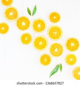 Creative scandinavian style flat lay top view of fresh orange fruit slices on white wooden table background with copy space. Minimal summer fresh citrus pattern for blog or recipe book